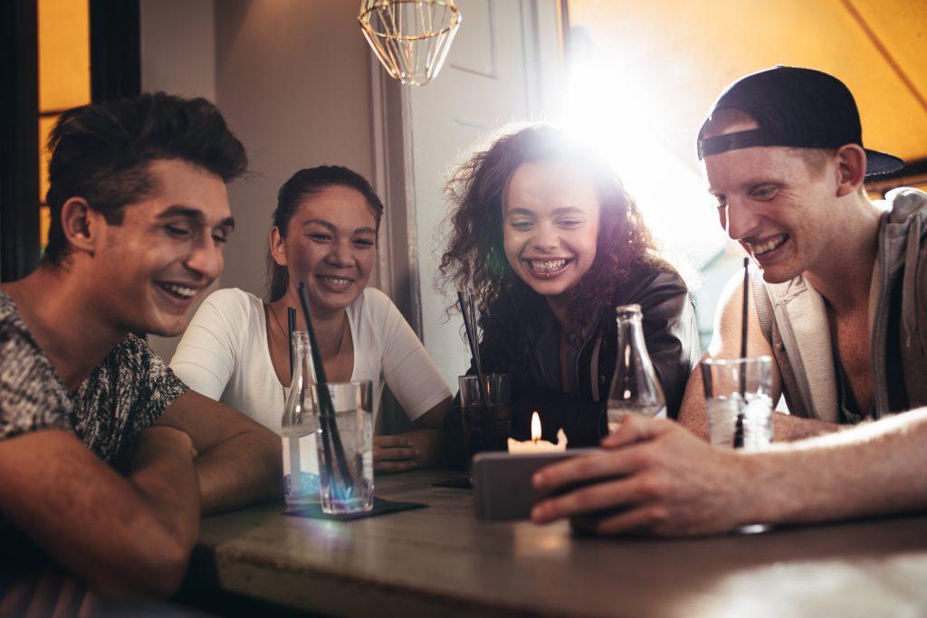 Groupe d'amis assis dans un café et souriant. Jeune hommr montrant quelque chose à ses amis sur son smartphone